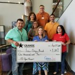 Photo of Texas Diaper Bank team accepting a giant check from Grande Communications